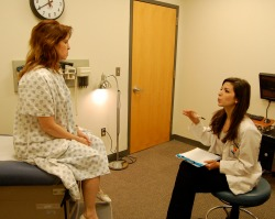 A med student talks to a standardized patient sitting on an exam table