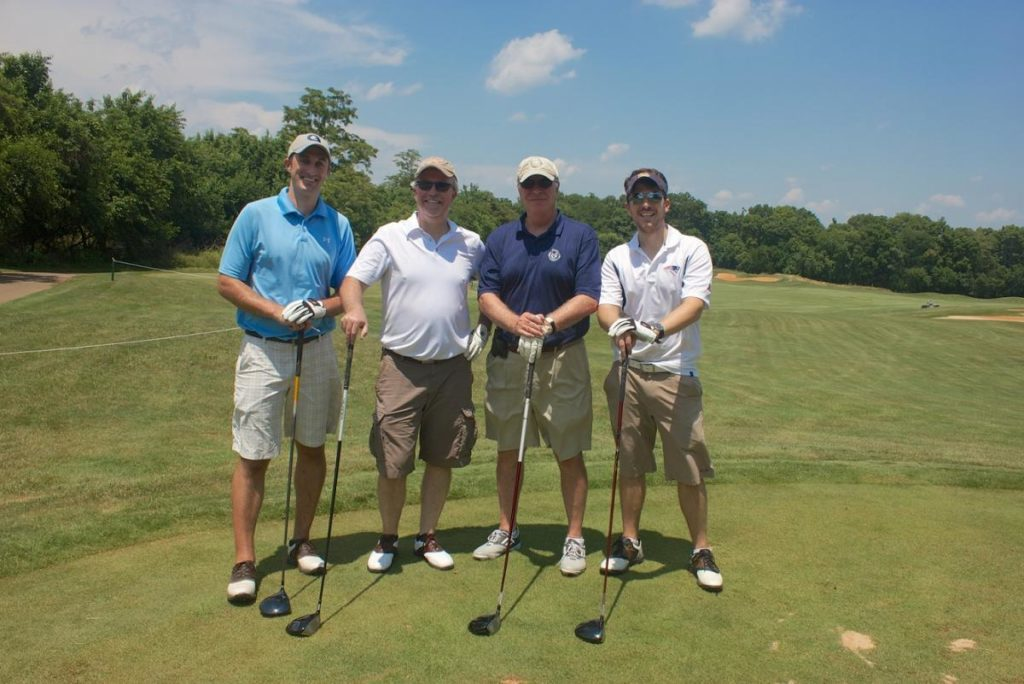 Four golfers stand on the green