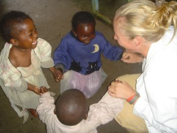 A medical student in white coat with three young African children
