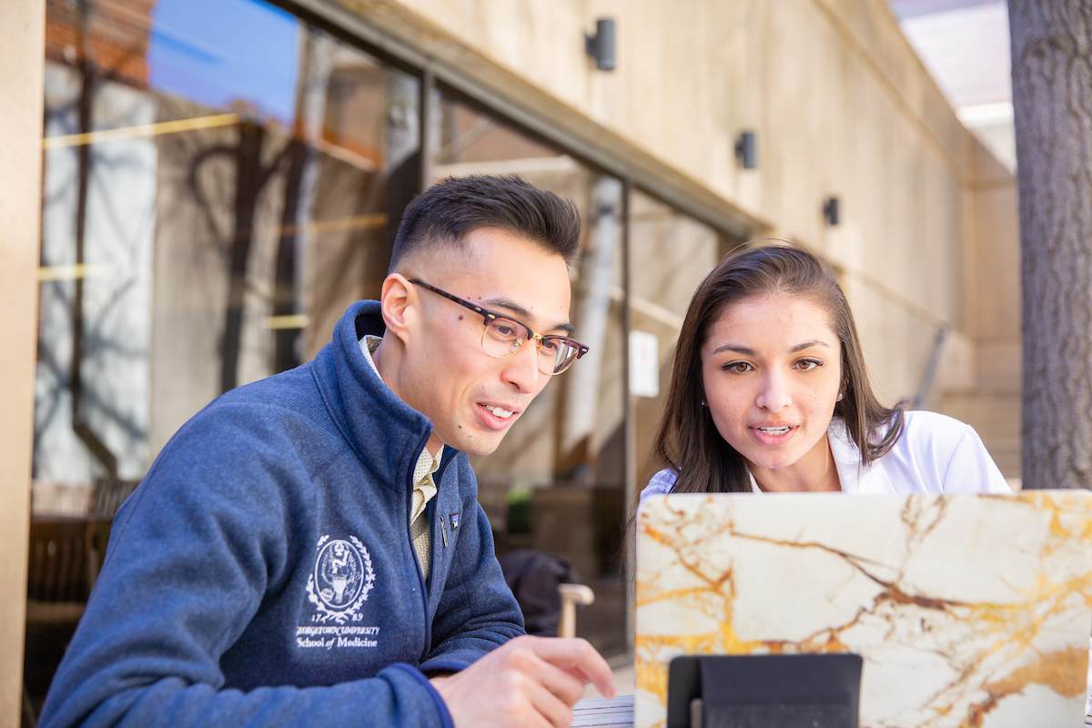 Two medical students converse before a laptop while seated outdoors
