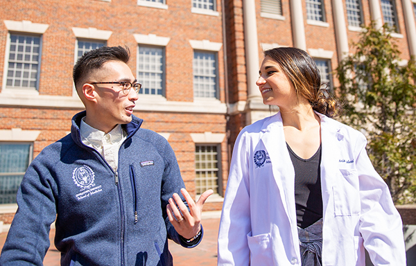 Two medical students walk together outdoors