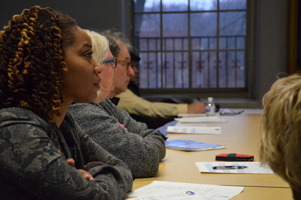 photo showing a row of attentive people sitting at a table at a seminar.