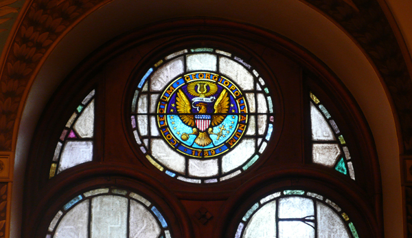 Georgetown University Seal in a stained glass window frame.