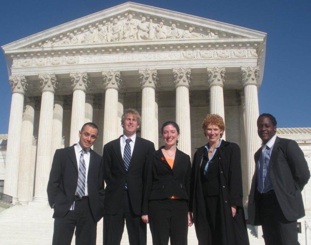 A group of five students and professors stand on the front steps outside the Supreme Court Building.