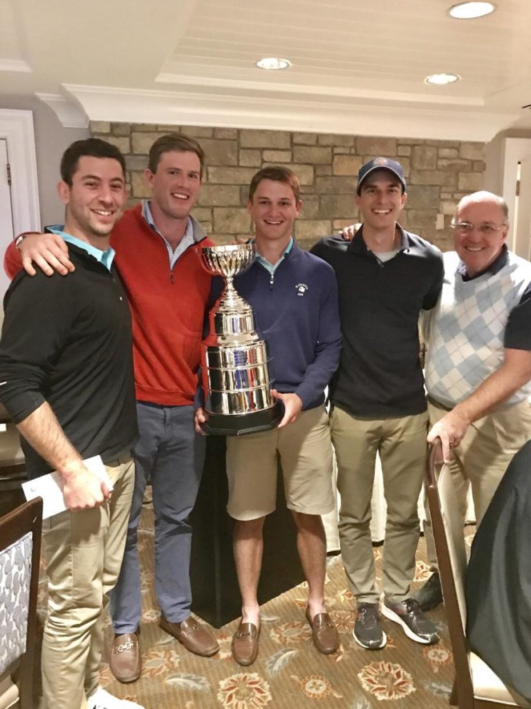 Five golf tournament participants stand with a trophy
