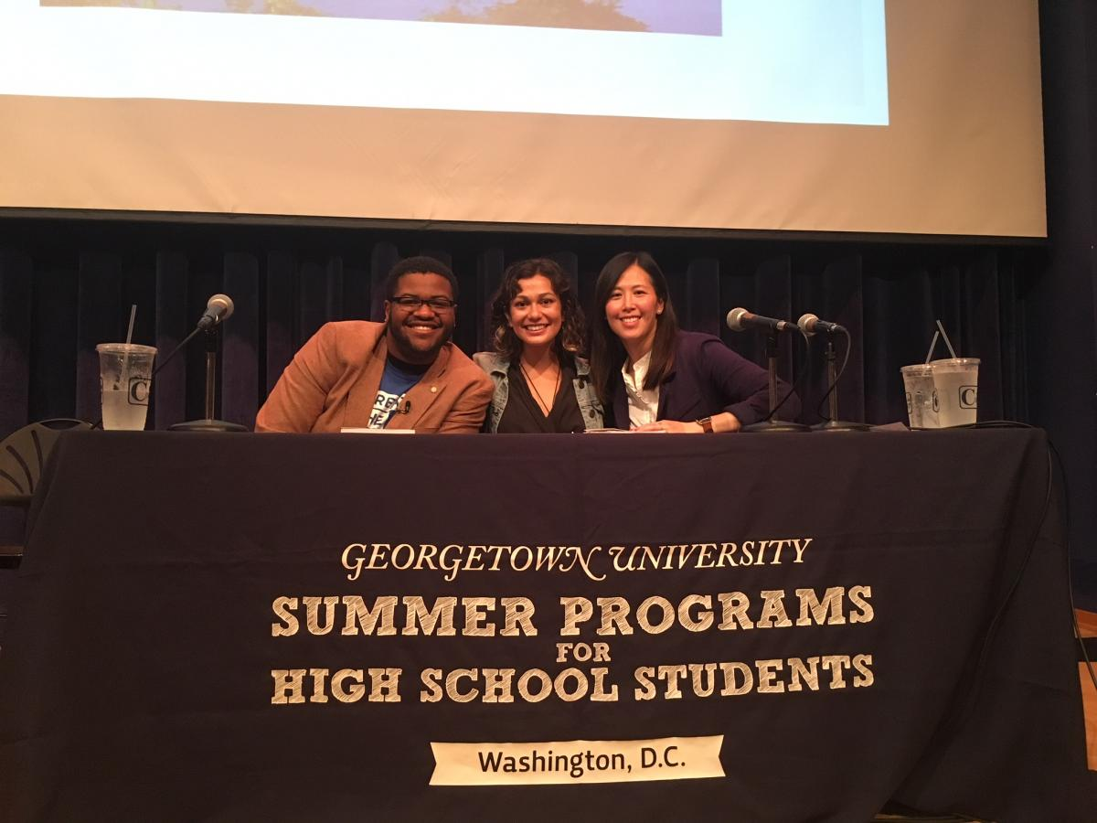 """Picture of 1 male and 2 females in front of table that says """" Georgetown University Summer Programs for High School Students"""""""
