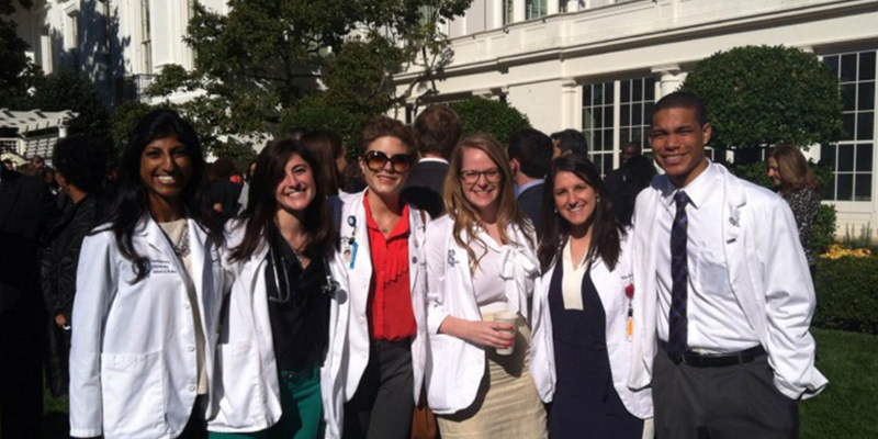 A group of students in white coats on the White House grounds