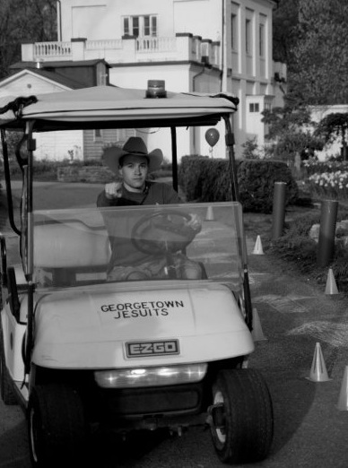 A volunteer driving a golf cart points at the camera