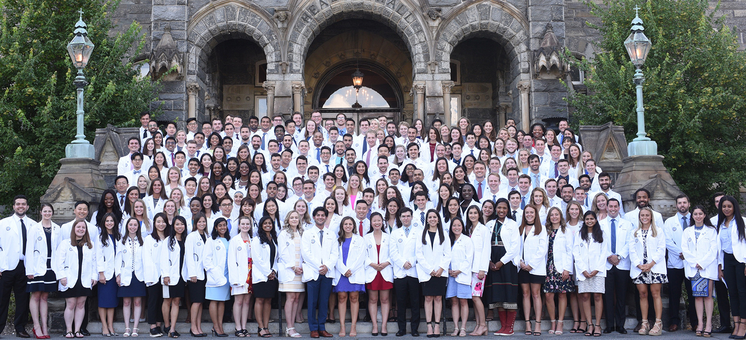 School of Medicine students, Class of 2023 stand en masse on the steps of Healy Hall