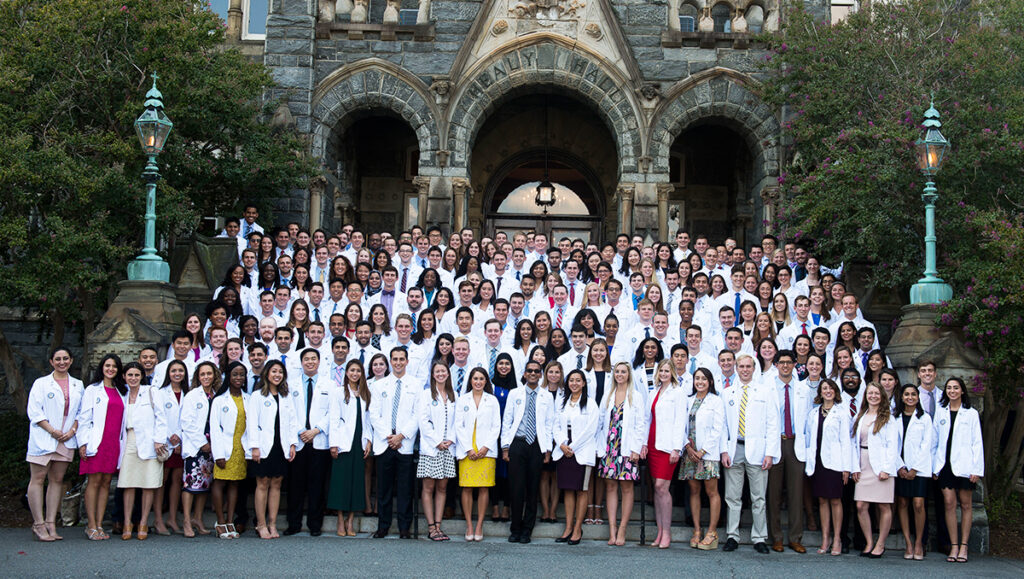 The class of 2021 stands in a large group on the steps of Healy Hall following their White Coat Ceremony