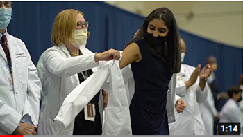 A student receives her White Coat